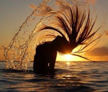 海に沈む夕日と水しぶきを上げる女性